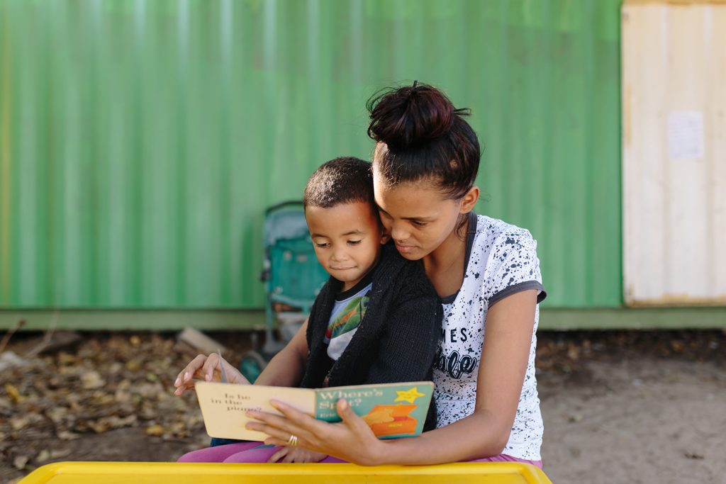 mother reading with her son on her lap