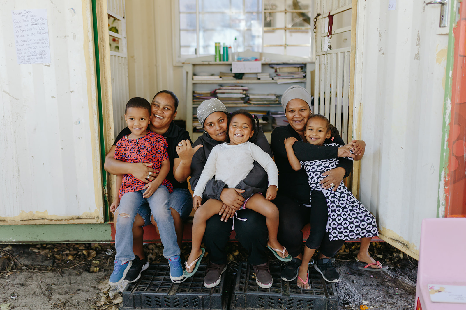 three parents with their children on their laps in front of the classroom container