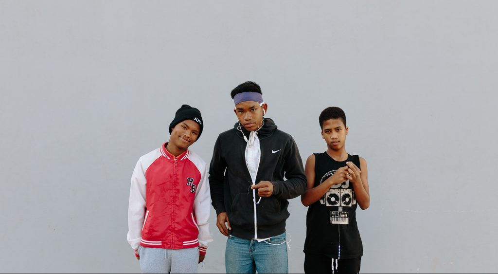 three boys from the residential facility standing in front of grey background