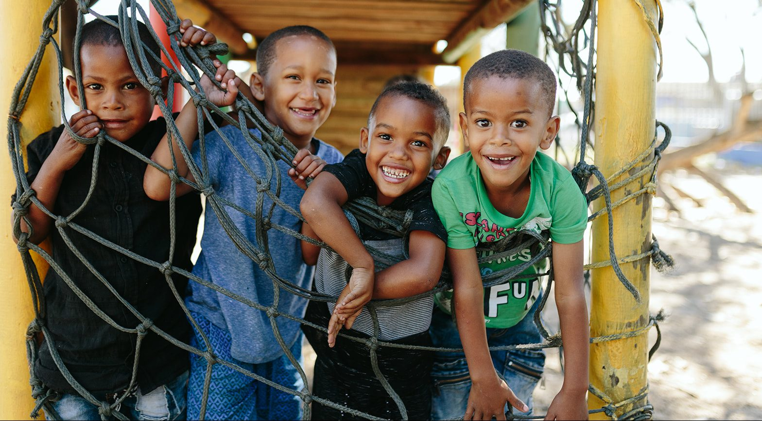 Four young boys hanging on a jungle gym
